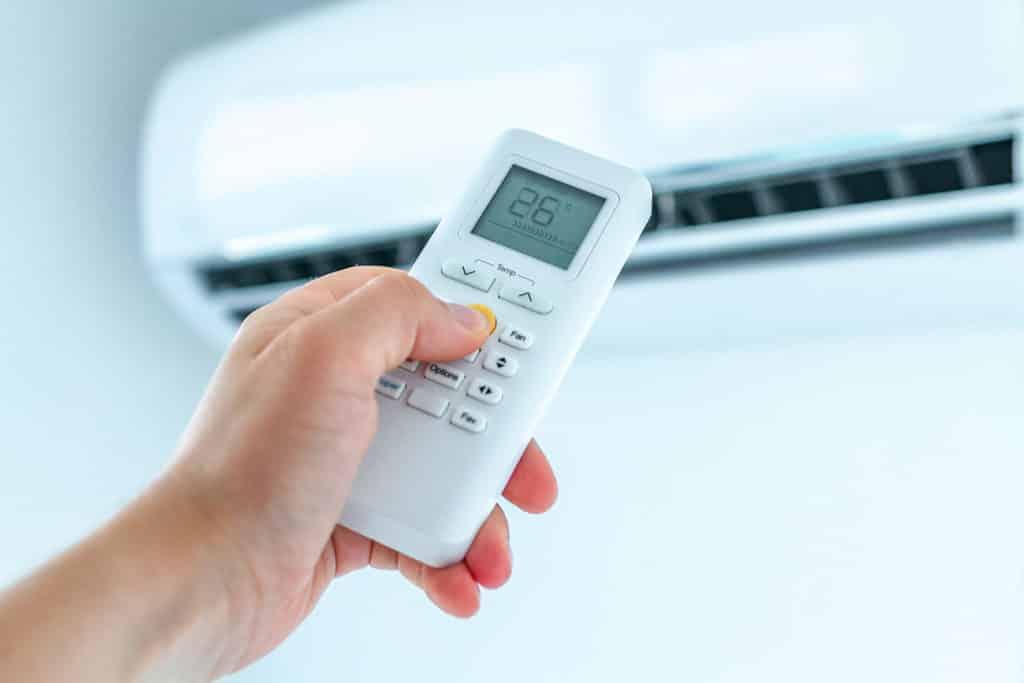 Man using an air con remote   LCM Air Conditioning